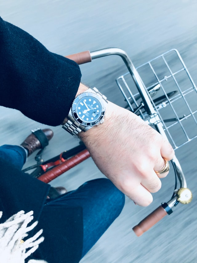 Wristshow Man wearing rolex and biking