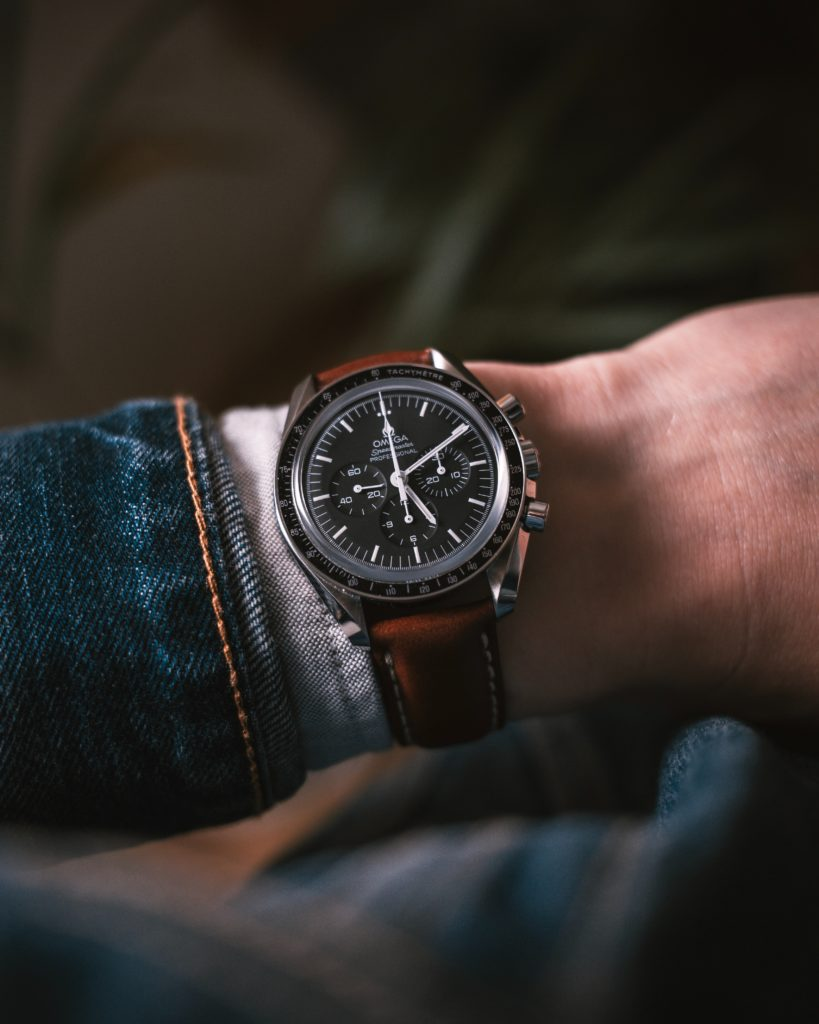 Omega speedmaster with leather strap on a man wrist wearing jeanns